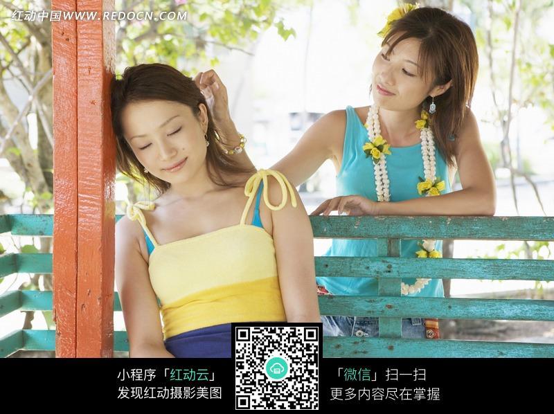 木椅上休息的美女和摸她头发的女伴