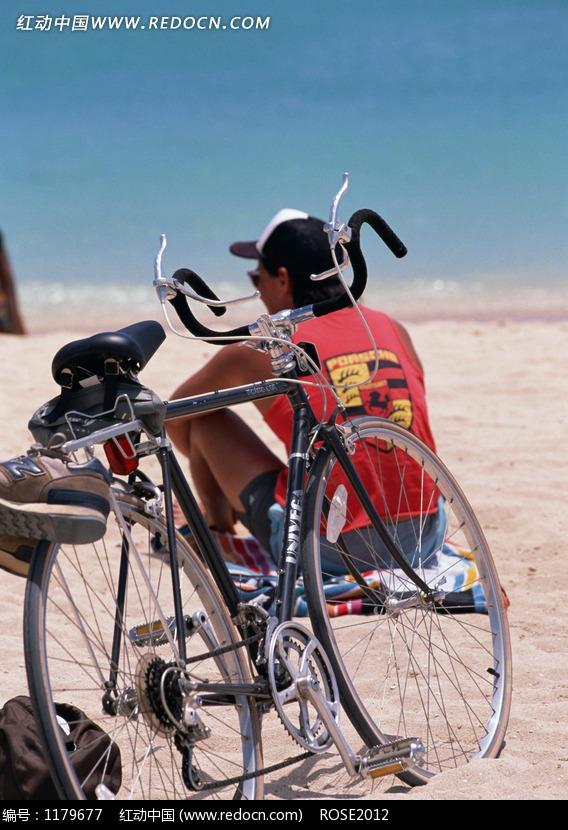 背坐在沙滩上男人背影和一辆自行车