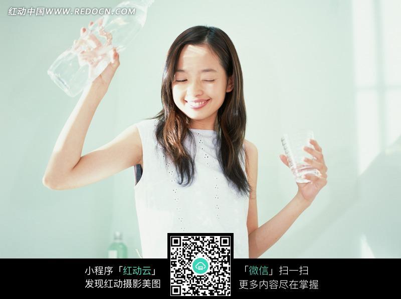 阳光下闭眼举着水瓶和水杯的美女设计图片