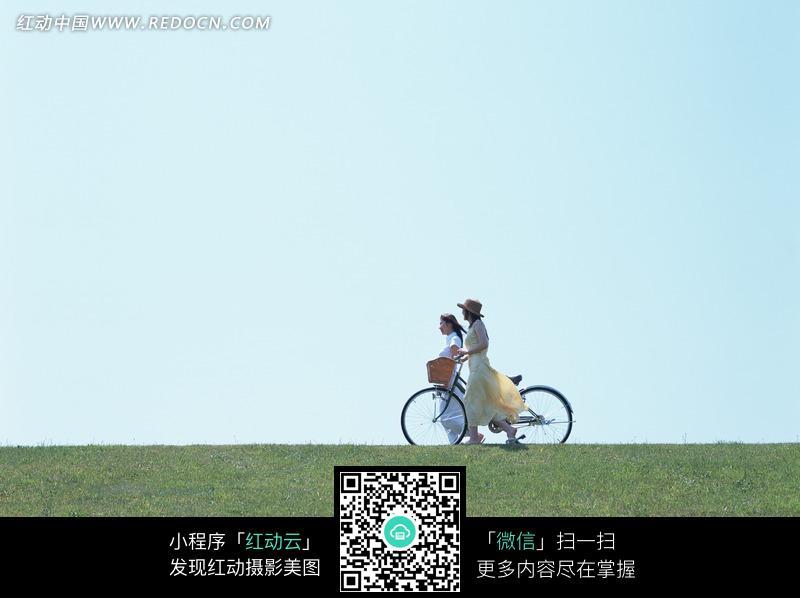 草地上两个推着自行车的美女设计图片