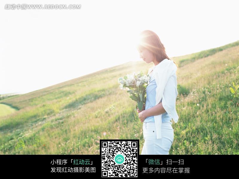 阳光下捧着一束野花走在草地上的美女图片 人