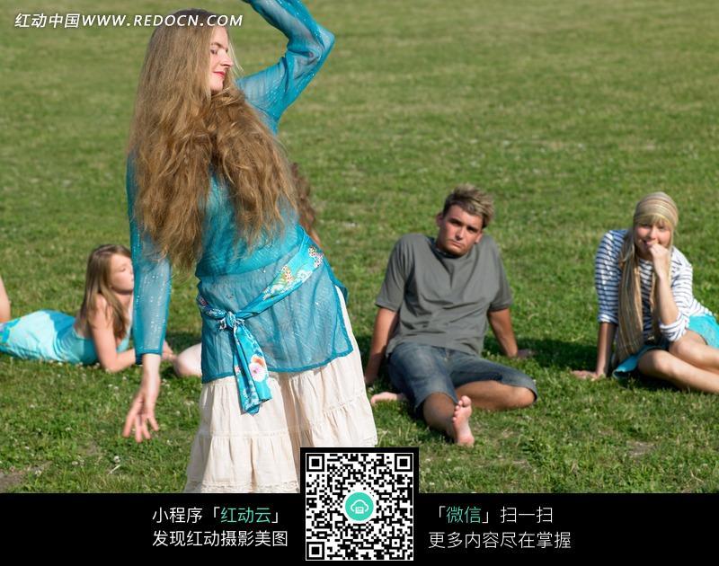 草地上穿着裙子的外国金发美女和旁边的男人图片