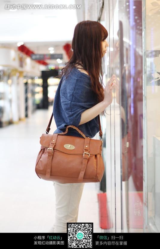 背着包包爬在玻璃上的美女图片(编号:1645972)