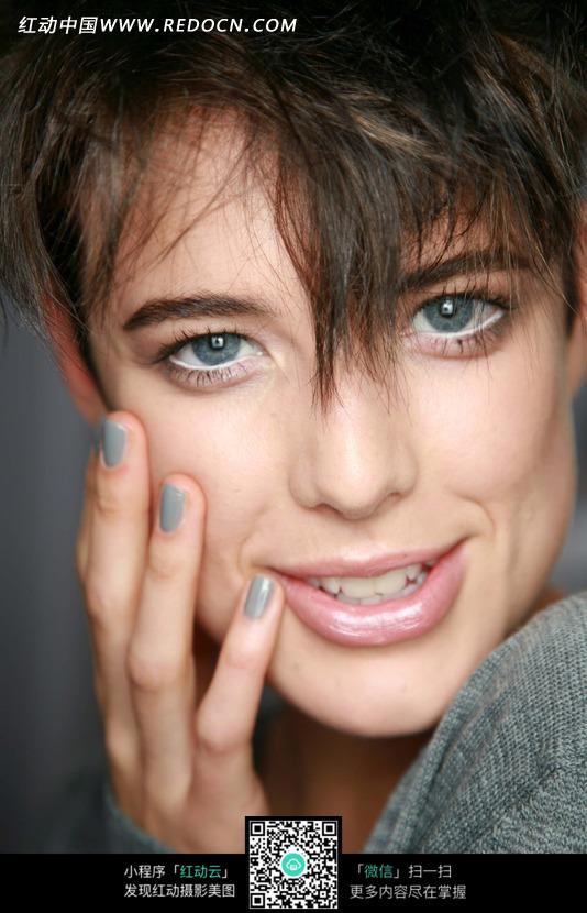 单手抚脸微笑的外国短发美女设计图片
